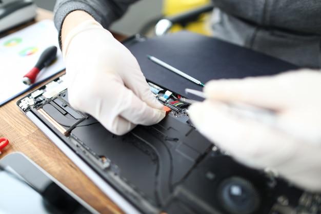 Técnico de reparo do laptop com ferramenta