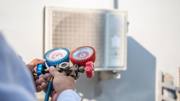Técnico de reparos de ar usando manômetro múltiplo para encher condicionadores de ar de fábrica