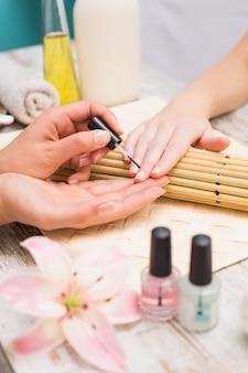 Técnico de unha dando ao cliente uma manicure
