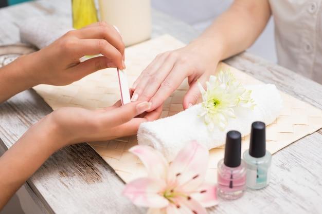Técnico de unha que dá ao cliente uma manicure
