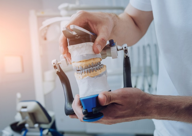 Técnico dental trabalhando com articulador no laboratório dental