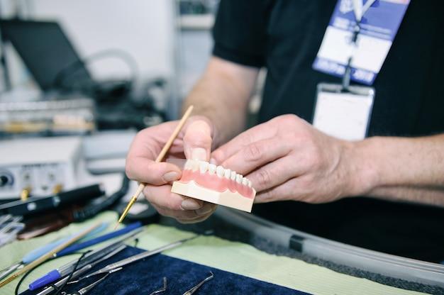 Técnico dentário realizando próteses dentárias médicas em laboratório
