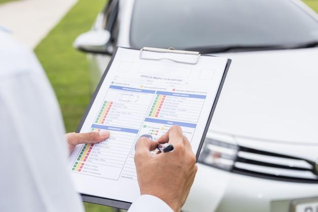 Técnico do carro que guarda o papel da lista de verificação na frente do carro. para o conceito de reparação de automóveis