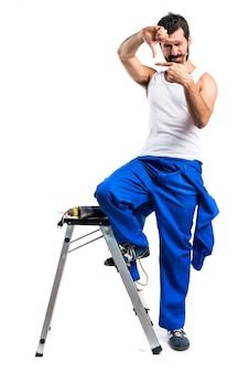 Técnico elétrico jovem com uma broca com foco nos dedos