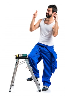 Técnico elétrico jovem com uma broca com os dedos cruzados