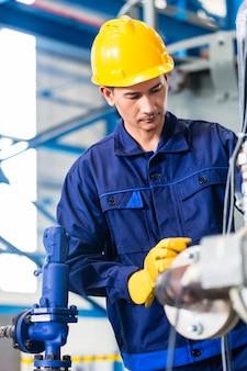 Técnico em fábrica asiática em manutenção de máquina trabalhando com chave inglesa