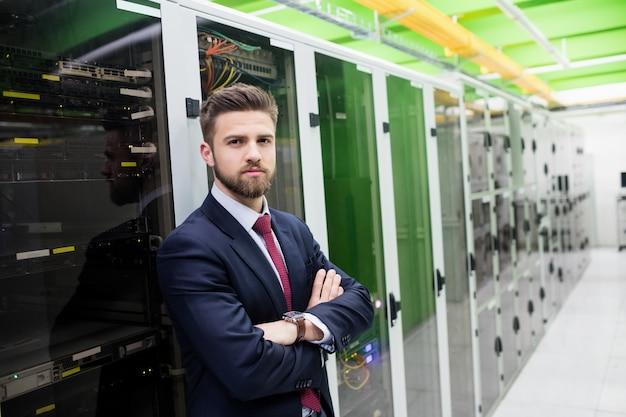 Técnico em pé com os braços cruzados em uma sala de servidores
