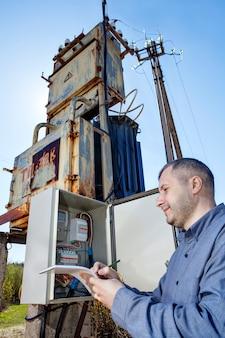 Técnico, escrevendo a leitura do medidor de eletricidade na área de transferência.