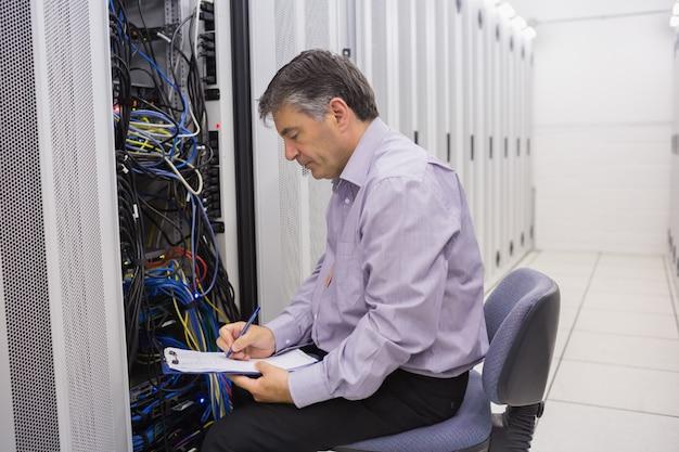 Técnico escrevendo notas nos servidores
