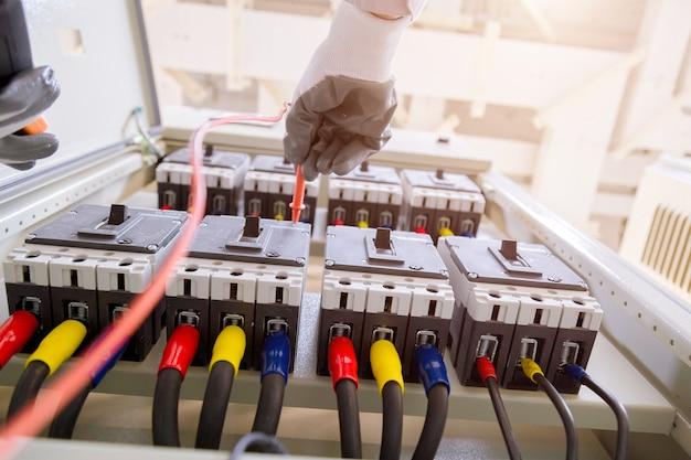 Técnico está medindo tensão ou corrente por voltímetro no painel de controle