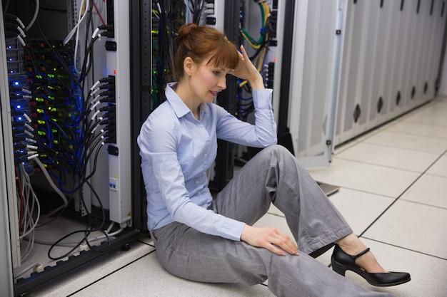 Técnico estressado sentado no chão ao lado do servidor aberto
