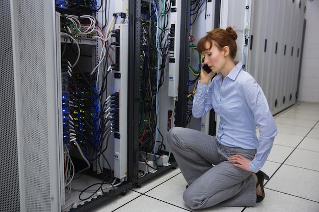 Técnico falando ao telefone enquanto analisa o servidor em um grande data center