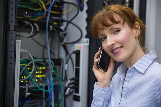 Técnico falando no telefone enquanto analisa o servidor