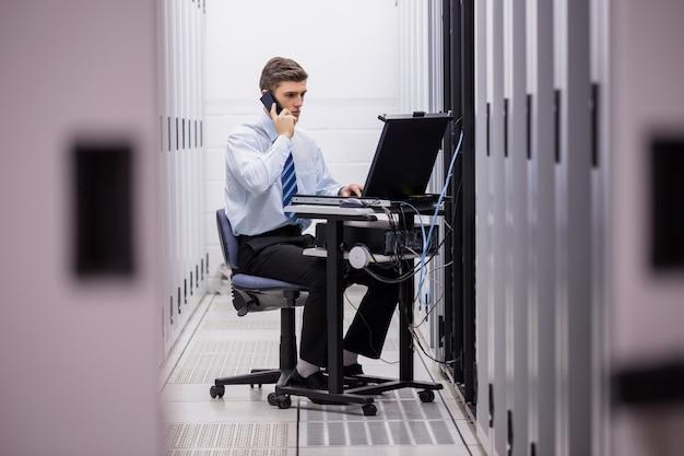 Técnico falando no telefone enquanto diagnostica servidores