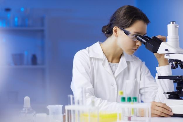 Técnico feminino olhando no microscópio