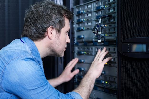 Técnico habilidoso e bonito em pé perto do servidor de dados e verificando os cabos usb enquanto faz seu trabalho