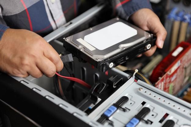 Técnico homem consertar ou atualizar o disco rígido no computador