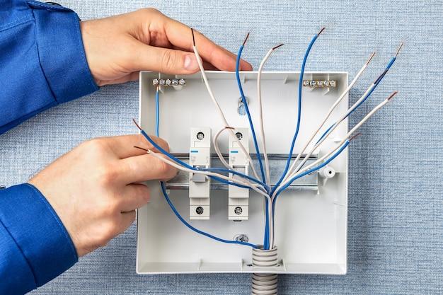 Técnico instalando novo quadro elétrico com fusíveis automáticos para fiação elétrica doméstica.