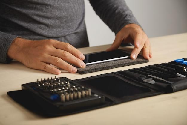 Técnico irreconhecível preparando smartphone quebrado para o processo de desmontagem