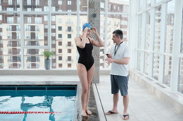 Técnico maduro com cronômetro parado à beira da piscina trabalhando com nadadora
