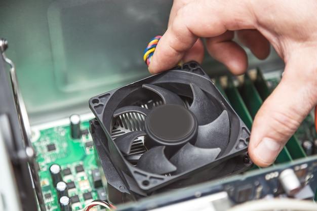 Técnico mãos instalando cpu cooler fan em uma placa-mãe do computador pc