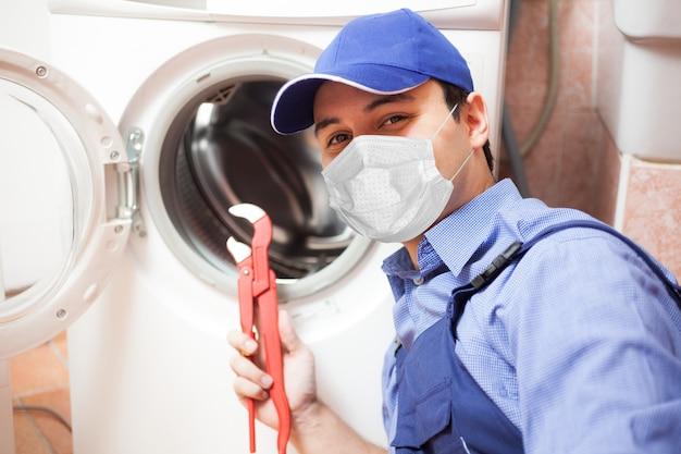 Técnico mascarado e sorridente consertando um conceito de máquina de lavar, covid ou coronavírus