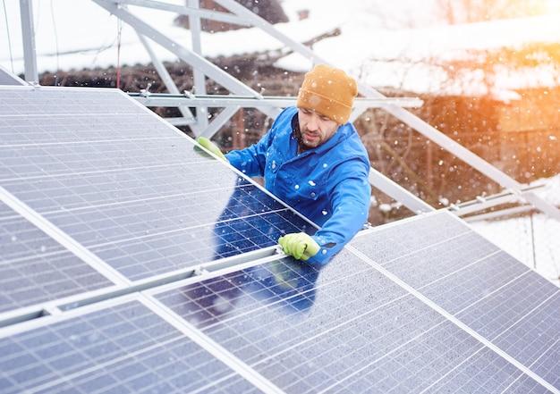 Técnico masculino forte no terno azul que instala módulos solares azuis fotovoltaicos como fonte de energia renovável.