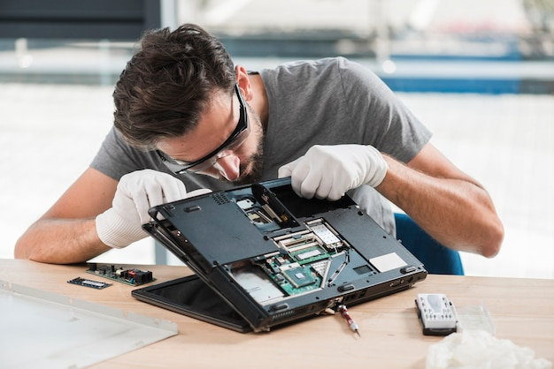 Técnico masculino novo que fixa o computador na mesa de madeira