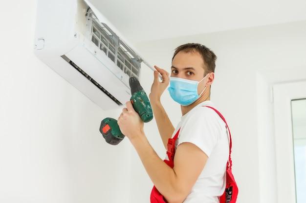 Técnico masculino que limpa o condicionador de ar dentro de casa