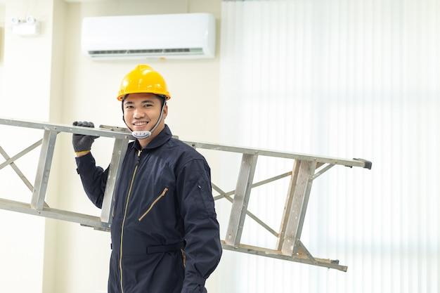 Técnico masculino que repara o uniforme da segurança do condicionador de ar dentro.