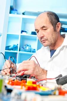 Técnico masculino sênior testa equipamentos eletrônicos