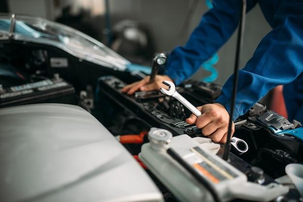 Técnico masculino trabalha com motor de carro.