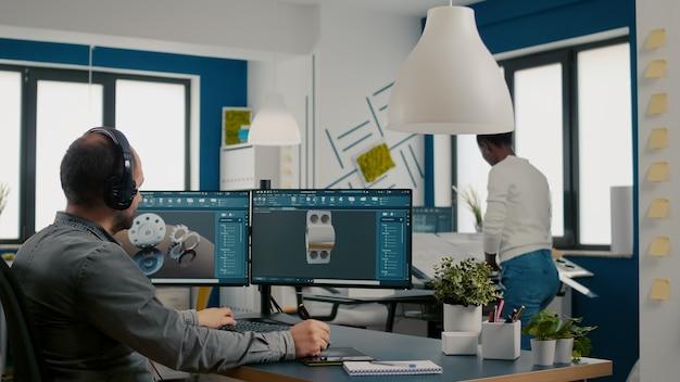 Técnico mecânico trabalhando em software cad usando computador com dois monitores inovando um protótipo de motor eficiente e ecologicamente correto