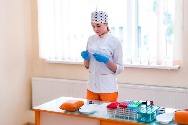 Técnico médico segurando o tubo de sangue no laboratório de pesquisa. equipamento médico. teste de sangue