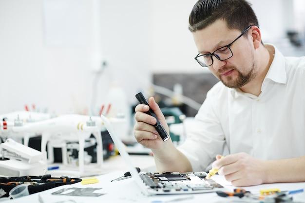 Técnico moderno inspecionando laptop com lanterna