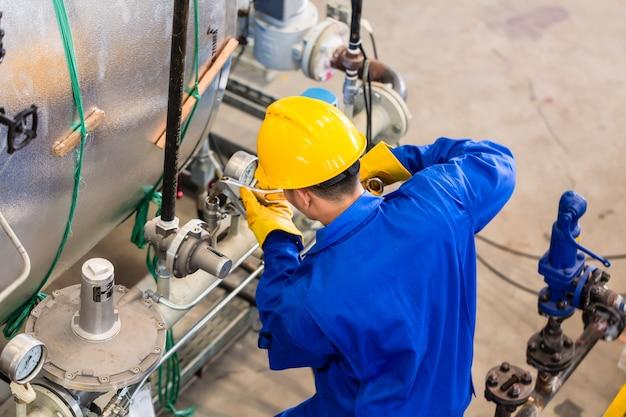 Técnico na fábrica na manutenção da máquina trabalhando com a chave inglesa, vista superior do homem
