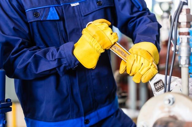 Técnico na fábrica na manutenção da máquina trabalhando com chave inglesa
