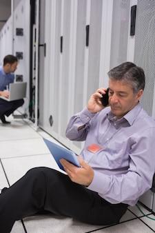 Técnico no telefone fazendo manutenção do servidor com tablet pc