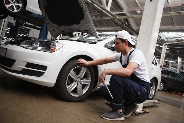 Técnico profissional de manutenção automotiva examinando rodas de um automóvel