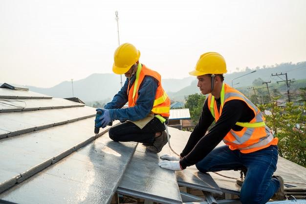Técnico profissional instala telhado novo no telhado, ferramentas de telhado, segure a ferramenta do parafuso de acionamento na mão.