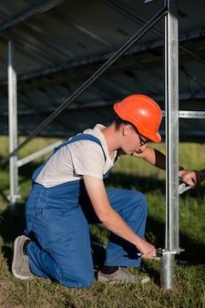 Técnico que instala a fundação do painel solar com pilhas helicoidais.
