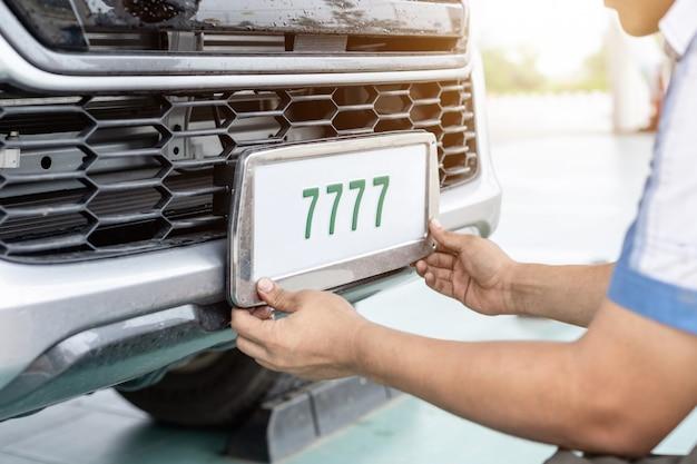Técnico que muda o número da placa do carro no centro de serviço