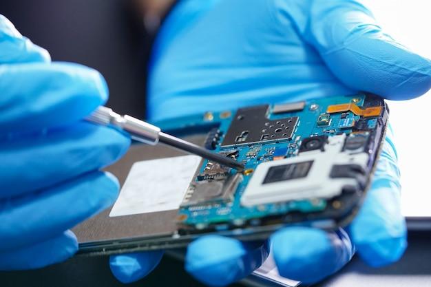 Técnico que repara a placa principal do micro circuito do smartphone.