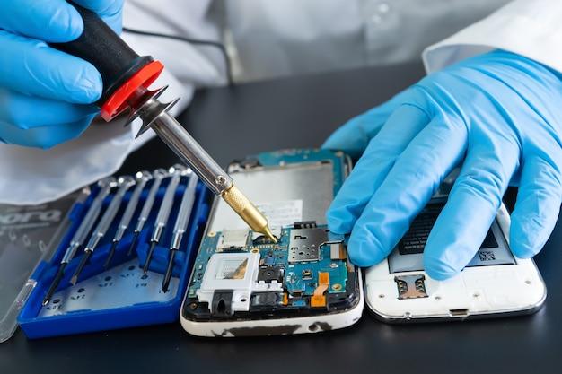 Técnico que repara o interior do telefone celular com o ferro de solda. circuito integrado. o conceito de dados, hardware, tecnologia.