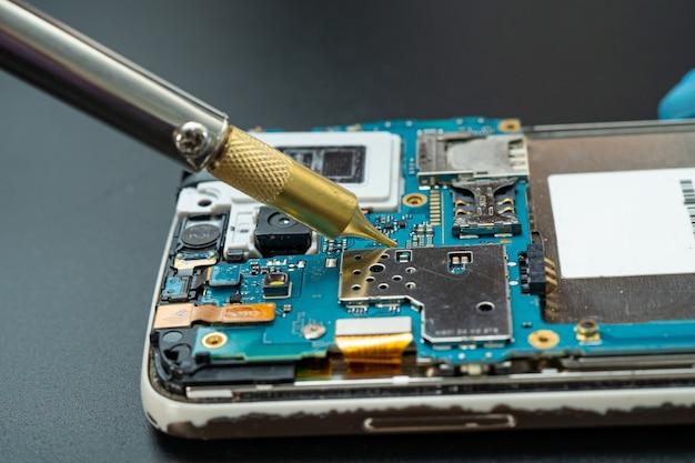 Técnico que repara o interior do telefone celular com o ferro de solda.