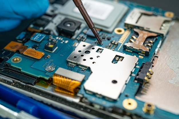 Técnico que repara o interior do telefone móvel com o ferro de solda. circuito integrado. o conceito de dados, hardware, tecnologia.