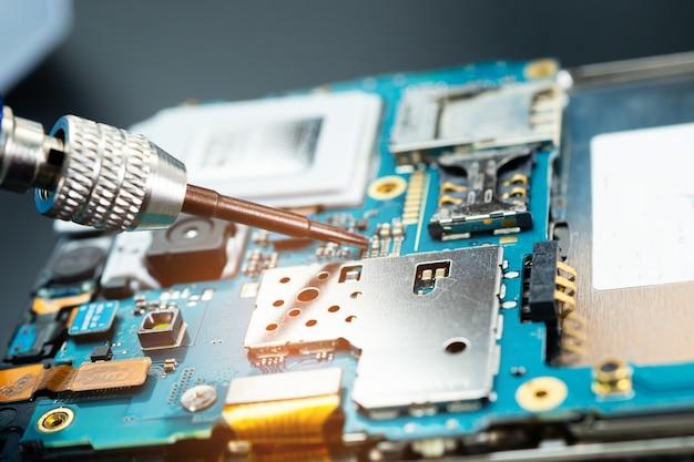Técnico que repara o interior do telefone móvel com o ferro de solda.