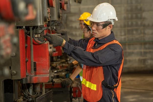 Técnico que trabalha na fábrica, engenharia da indústria, usando controle uniforme de segurança, operando a máquina de retificação de torno.