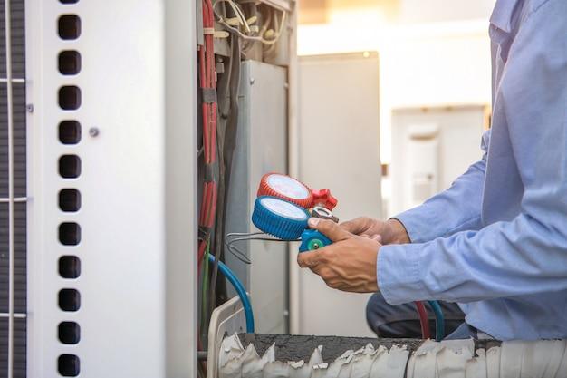 Técnico que usa equipamento de medição para encher condicionadores de ar e verificar a unidade de compressor de ar externo.
