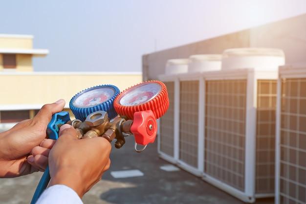 Técnico que usa equipamento de medição para encher condicionadores de ar industriais de fábricas.